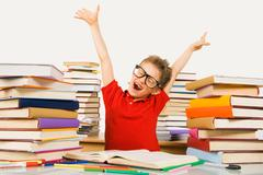 joyful lad raising his arms while preparing lessons and screaming - stock photo