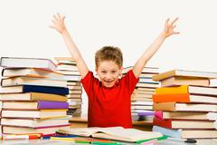 Photo of joyful pupil raising arms in excitement and looking at camera with smil Stock Photos