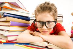 Portrait of pensive lad in eyeglasses putting his head on open book Stock Photos