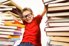 photo of schoolkid looking at camera between two heaps of colorful books - stock photo