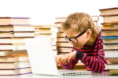 portrait of pensive lad in eyeglasses typing on laptop between piles of books - stock photo