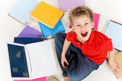 above view of screaming kid sitting among textbooks with laptop near by - stock photo