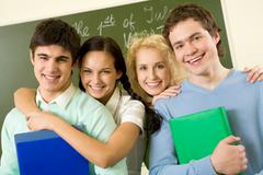 Portrait of happy students standing next to each other and looking at camera wit Stock Photos