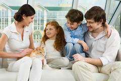 Portrait of careful parents and their two children enjoying weekend day at home Stock Photos