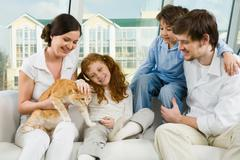 photo of cute girl caressing pet on her mother's knees - stock photo