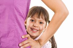 Face of happy child looking through her mother arm bent in elbow over white back Stock Photos