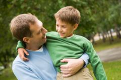 Stock Photo of image of happy man holding his son on hands outside