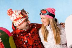 portrait of happy couple with snowboards communicating in snowfall - stock photo