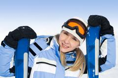 Portrait of pretty skier in blue overalls looking at camera with smile Stock Photos