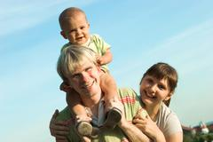 Photo of father with baby and mother looking at camera in open air Stock Photos