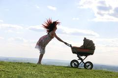 Emotional woman standing on green grassland and having fun while holding pram wi Stock Photos