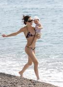Photo of slim female in bikini walking down seashore with adorable infant at sum Stock Photos