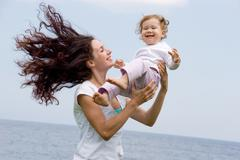 Joyful female playing with adorable infant on fresh air at summer Stock Photos