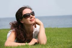 Portrait of pretty young lady relaxing on green grassland and looking aside thro Stock Photos