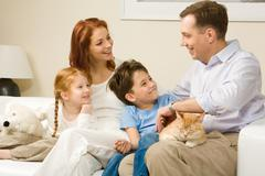 Friendly family members sitting on comfortable sofa and communicating at home Stock Photos