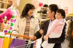 Portrait of friendly family shopping together with shop window at background Stock Photos