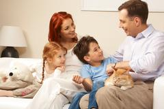 curious children and woman looking attentively at handsome man while relaxing on - stock photo