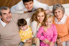 above shot of senior and young couples with two children sitting on sofa and loo - stock photo