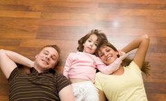 View from above of cheerful family members lying on the floor and looking at cam Stock Photos