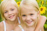 Stock Photo of portrait of cute girl embracing her twin sister and both looking at camera with