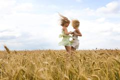 portrait of energetic twin sisters whirling in wheat field and having fun - stock photo