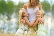 Stock Photo of twin sisters embracing their mother with smiles in wheat field
