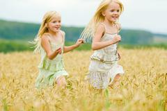 portrait of happy girl running down wheat field with her twin sister behind - stock photo
