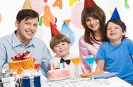 Stock Photo of portrait of cute boy having his birthday party with parents and older brother