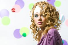 Portrait of glamorous blonde with wavy hair-style looking at camera on colorful Stock Photos
