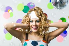 Portrait of happy female with wavy hair-style among soap bubbles looking at came Stock Photos