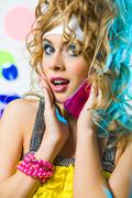 Photo of cute blonde with wavy hair talking on cellular phone and looking at cam Stock Photos