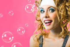 Photo of happy girl surrounded by soap bubbles on pink background Stock Photos