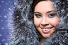 portrait of beautiful female wearing fur cap and smiling - stock photo