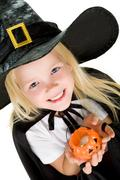 portrait of girl in witch costume and small pumpkin candle in hands - stock photo