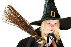 Portrait of girl in halloween costume and broom with frightening expression Stock Photos