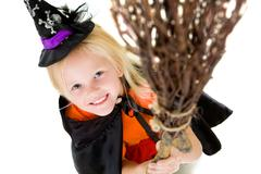 above angle of girl in halloween costume and broom smilling at camera - stock photo
