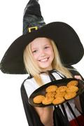 photo of girl in halloween costume holding tray with bisquits - stock photo