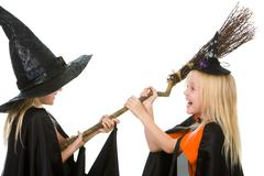 portrait of girl twins in black hats and black clothing sharing broom - stock photo