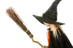 photo of girl in witch costume holding broom - stock photo
