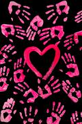 Stock Photo of image of heart shape of red color surrounded by hand prints on black background
