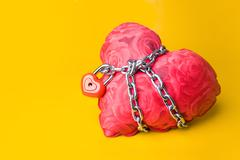 creative image of soft toy heart bound with chain and small padlock - stock photo