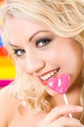 face of lovely lady with pink lollypop looking at camera - stock photo