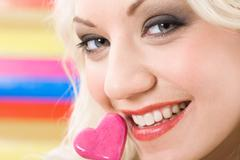 close-up of beautiful female face with lollypop by her mouth looking at you - stock photo