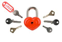 image of red heart-shaped lock with several keys around on white background - stock photo
