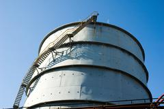 below shot of big modern plant pipe with blue sky above - stock photo