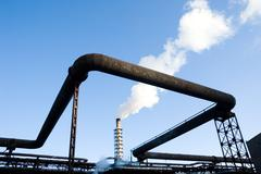 Image of pipes of large modern factory on background of blue sky Stock Photos