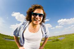 portrait of young man in sunglasses looking at camera on background of countrysi - stock photo