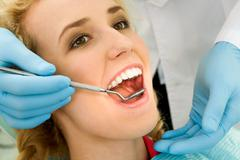 close-up of young woman during inspection of oral cavity with help of hook and m - stock photo