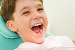 photo of youngster with his mouth wide open during checkup at the dentist's - stock photo