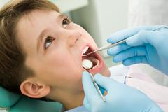 Close-up of little boy opening his mouth during dental checkup Stock Photos